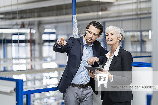 Geschäftsmann und leitende Geschäftsfrau mit Tablettengespräch in einer Fabrik