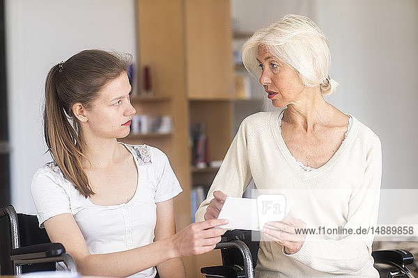 Mother and daughter in a wheelchair with a letter