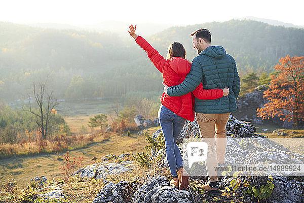 Rückansicht des glücklichen Paares bei einer Wanderung in den Bergen auf einem Felsen stehend