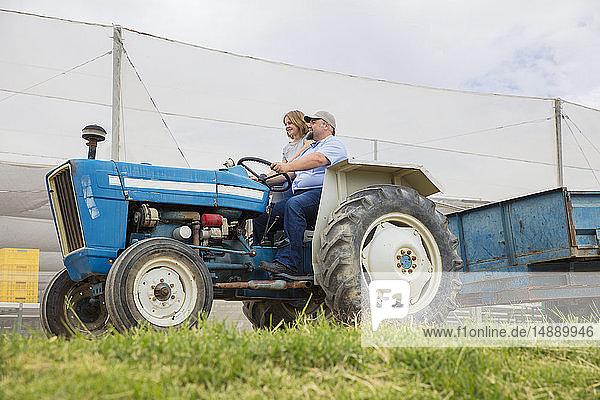 Landwirt zeigt seiner Tochter  wie man einen Traktor fährt
