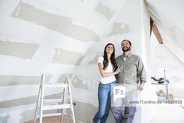 Zuversichtliches Paar steht auf dem Dachboden  der renoviert werden soll