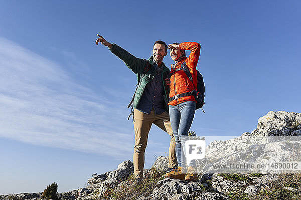 Happy couple on a hiking trip in the mountains standing on rock enjoying the view
