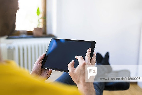 Close-up of man using tablet at home