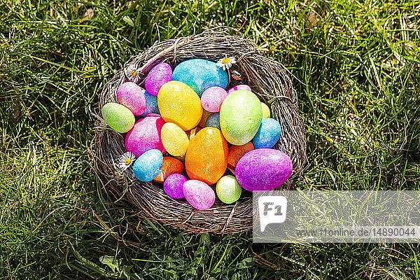 Bunte Ostereier in einem Nest auf Gras