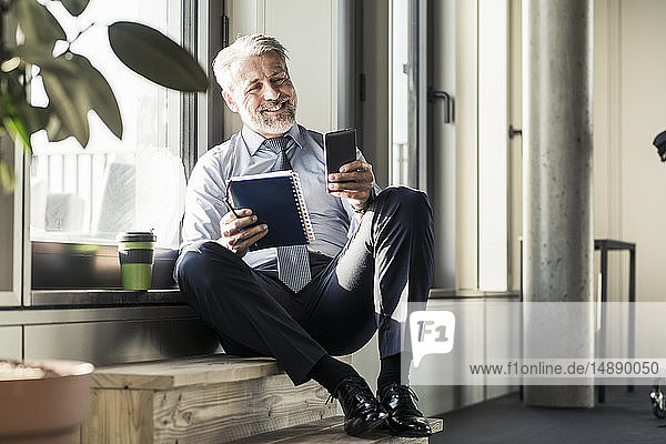 Smiling mature businessman sitting at the window with cell phone and notebook