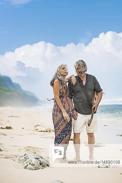 Älteres Hippie-Paar mit Gitarre am Strand stehend