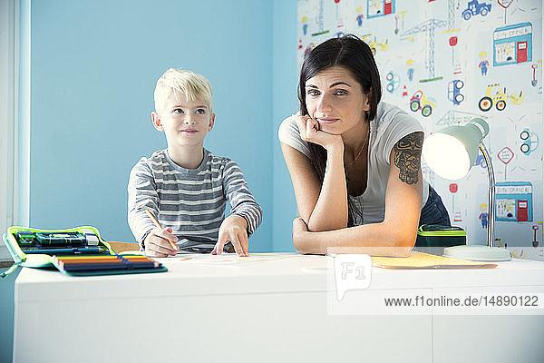 Porträt einer Mutter mit Sohn bei den Hausaufgaben am Schreibtisch