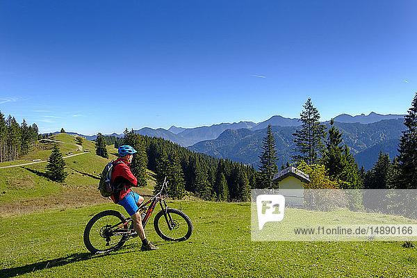 Deutschland  Mountainbiker mit Blick auf Hirschtalsattel  Aueralm mit Tegernseer Bergen bei Lenggries