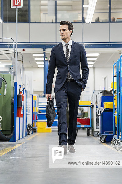 Businessman walking in a factory