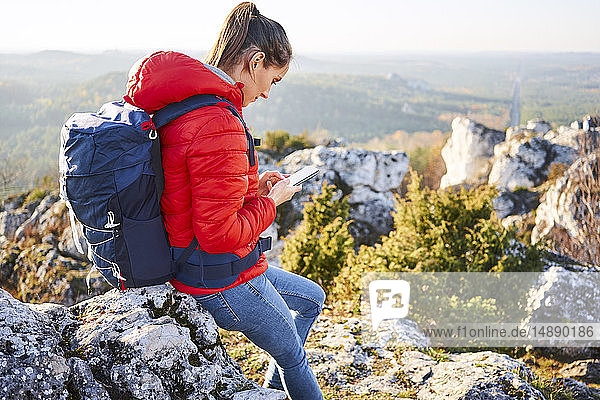 Woman on a hiking trip in the mountains checking cell phone