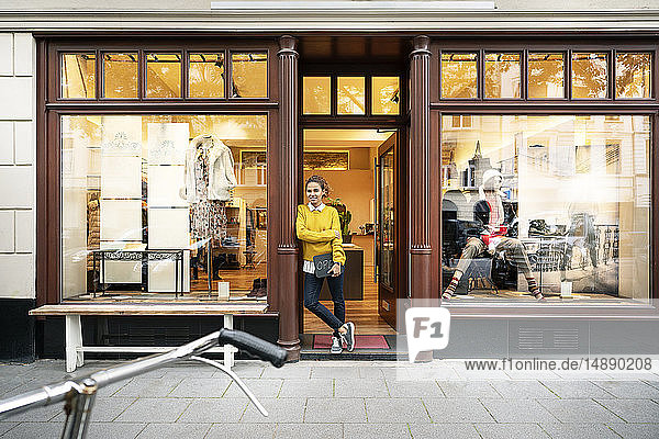 Young woman standing in door of a fashion store  holding laptop