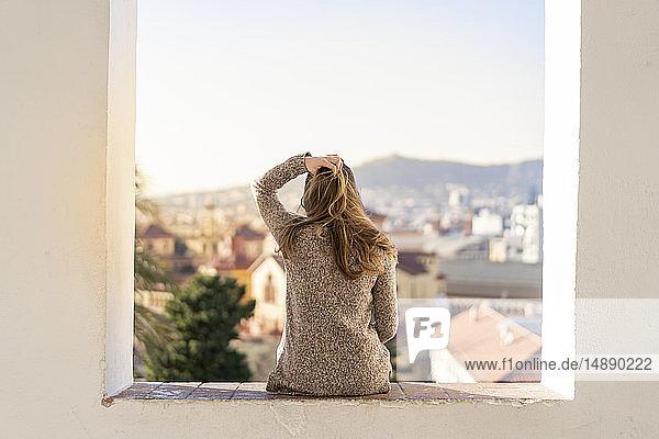 Rückansicht einer jungen Frau  die an einer Wand sitzt