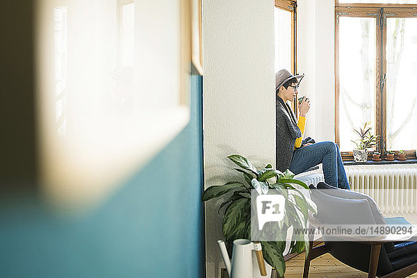 Woman sitting on windowsill in stylish apartment holding coffee mug