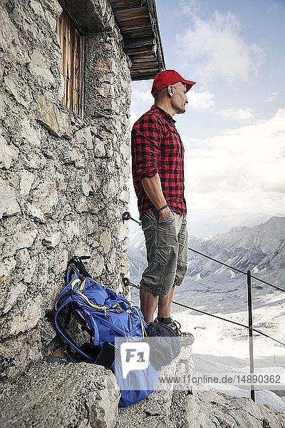 Österreich  Tirol  Mann auf Wanderung  steht an Berghütte und schaut auf Aussicht