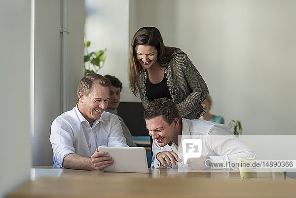 Happy colleagues looking at tablet in office