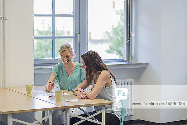 Zwei lächelnde Geschäftsfrauen arbeiten im Büro an einem Dokument