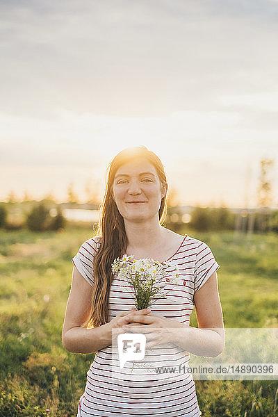 Porträt einer lächelnden jungen Frau  die bei Sonnenuntergang einen Strauss gepflückter Wildblumen hält