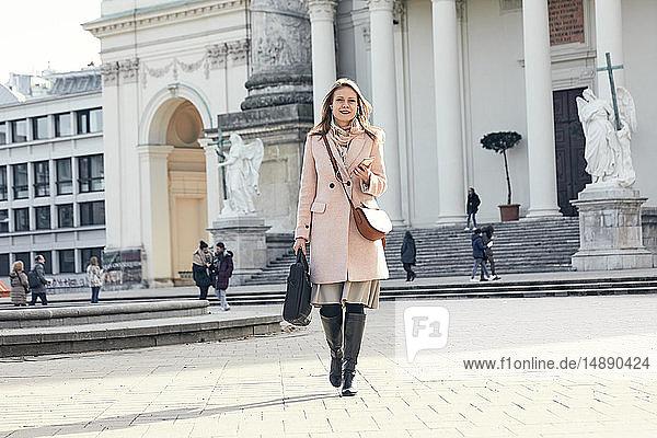 Austria  Vienna  Austria  Vienna  young businesswoman with laptop bag crossing Karlsplatz