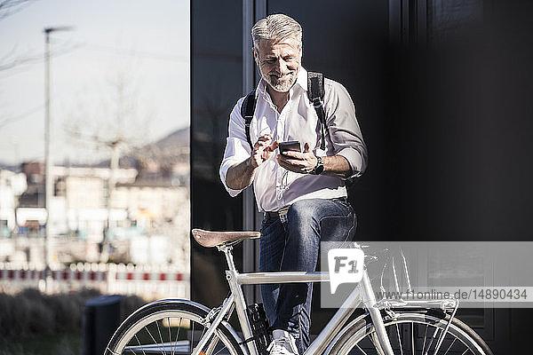 Lächelnder reifer Geschäftsmann mit Fahrrad und Kopfhörer mit Handy