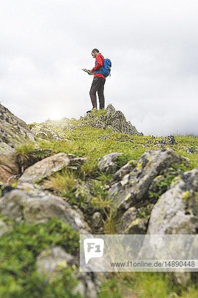 Mann steht auf einem Hügel und schaut auf seine Karte in den Karpaten  Rumänien