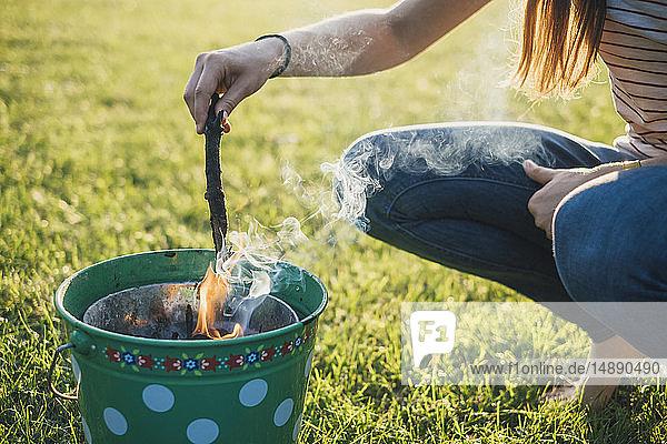 Frau beim Grillen auf einer Wiese  Teilansicht