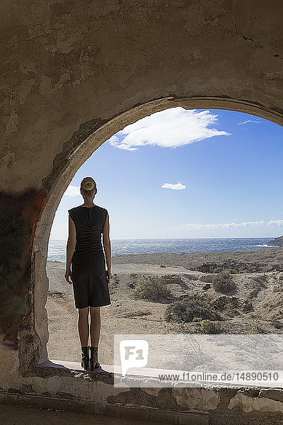 Spain  Tenerife  Abades  Sanatorio de Abona  woman standing at arched window in ghost town building
