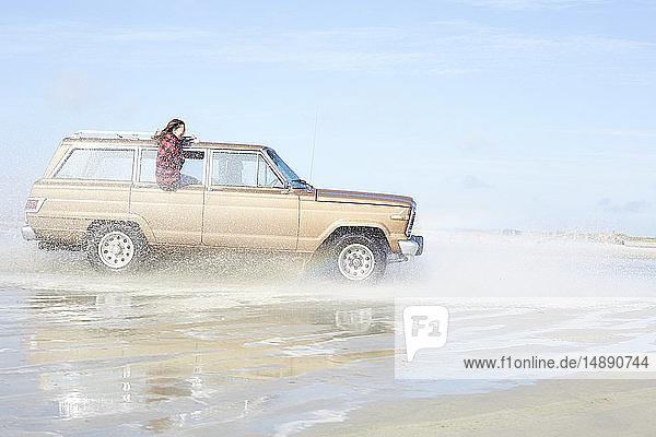 Deutschland  St. Peter-Ording  Mädchen lehnt sich aus dem Fenster eines Geländewagens  der am Strand durchs Wasser fährt