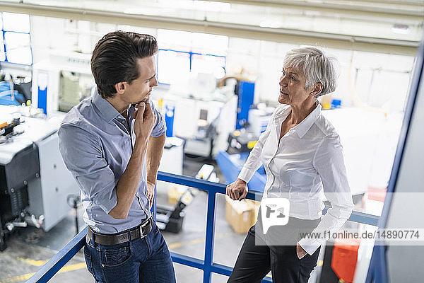 Geschäftsmann und leitende Geschäftsfrau im Gespräch in einer Fabrik