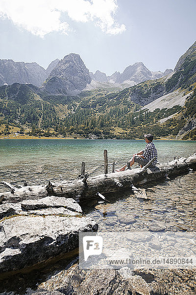 Austria  Tyrol  man sitting on tree trunk at lake Seebensee
