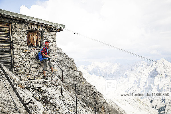 Österreich  Tirol  Mann auf einer Wanderung stehend auf einer Berghütte