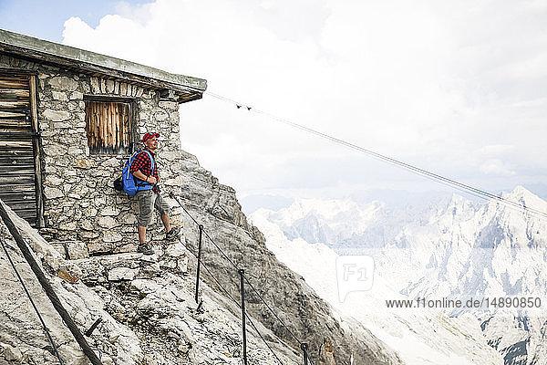 Austria  Tyrol  man on a hiking trip standing at mountain hut