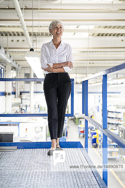 Confident senior businesswoman standing on upper floor in factory
