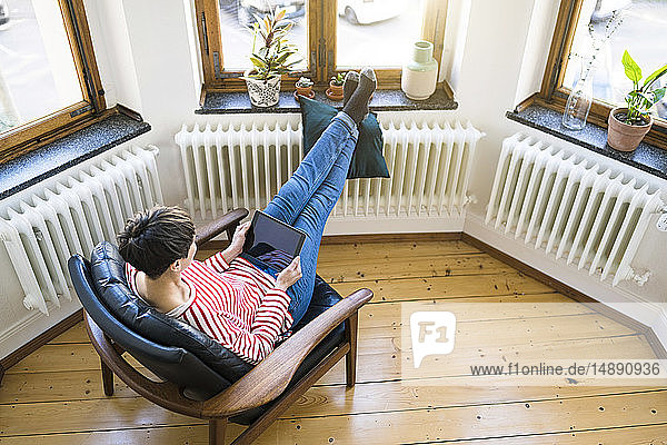 Short-haired woman relaxing in lounge chair holding tablet in stylish apartment