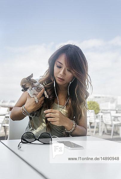 Porträt einer Frau  die mit ihrem Chihuahua-Welpen mit Kopfhörern und Smartphone im Straßencafé sitzt