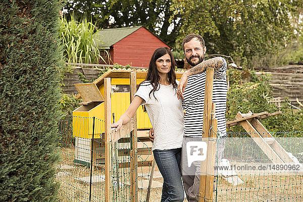 Porträt eines selbstbewussten Paares  das im Hühnerstall im Garten steht