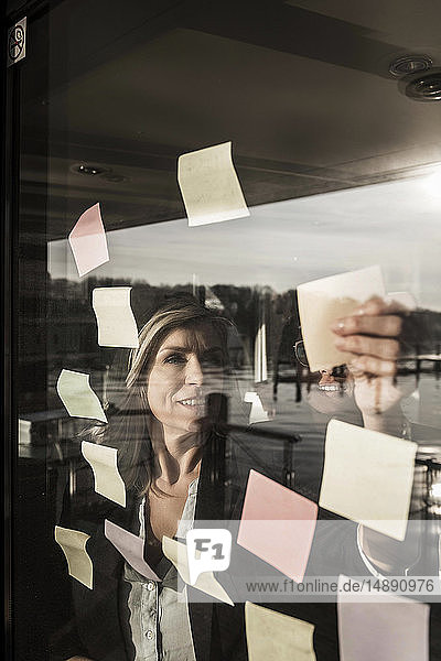 Zwei Geschäftsfrauen machen ein Brainstorming und kleben Haftnotizen an die Fensterscheibe