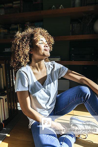 Junge Frau mit lockigem Haar sitzt auf dem Boden und genießt den Sonnenschein