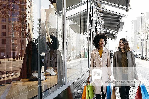 Zwei glückliche Frauen mit Einkaufstaschen gehen in der Stadt spazieren