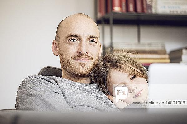 Vater und Tochter sitzen auf der Couch und benutzen einen Laptop