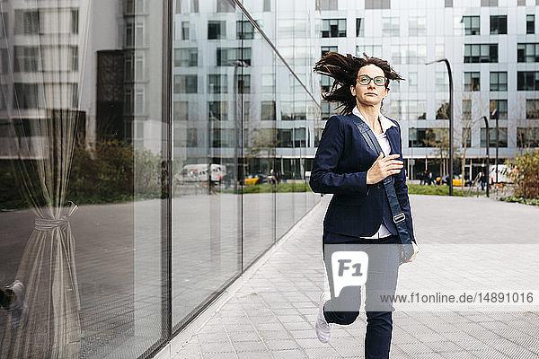 Geschäftsfrau  die vor einem Bürogebäude in der Stadt läuft