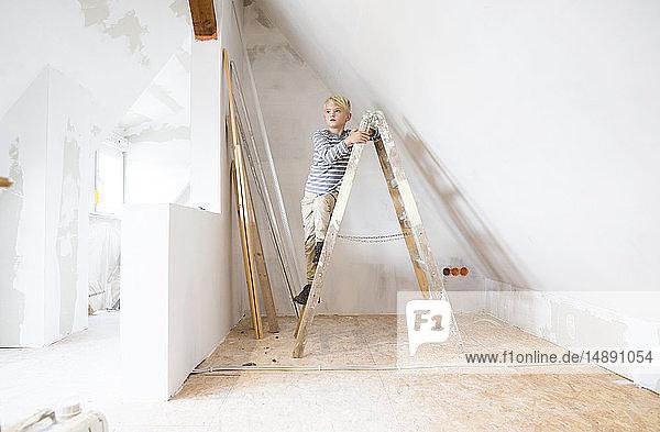 Junge steht auf Leiter auf dem Dachboden  der renoviert werden soll