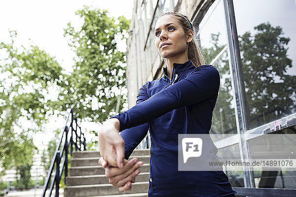 Sporty young woman stretching in city