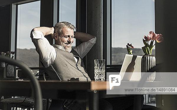 Lächelnder reifer Geschäftsmann mit Laptop im Büro  der eine Pause macht