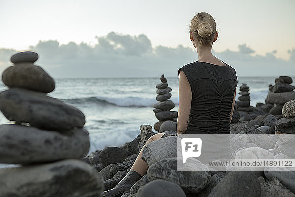 Spain  Tenerife  Costa Adeje  woman sitting between cairns at the coast