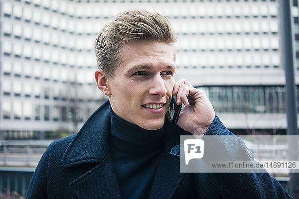 Porträt eines lächelnden jungen Mannes beim Telefonieren in der Stadt