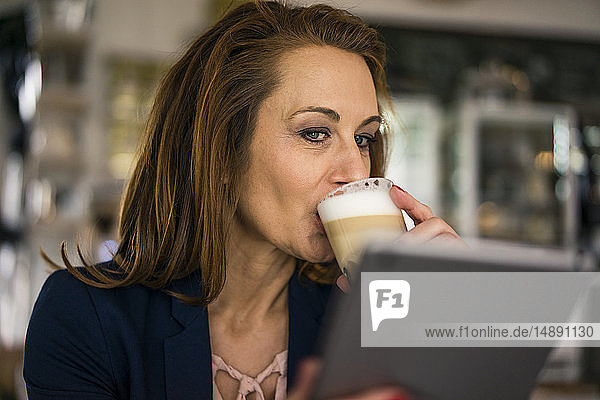 Businesswoman working in coffee shop  using digital tablet  drinking coffee