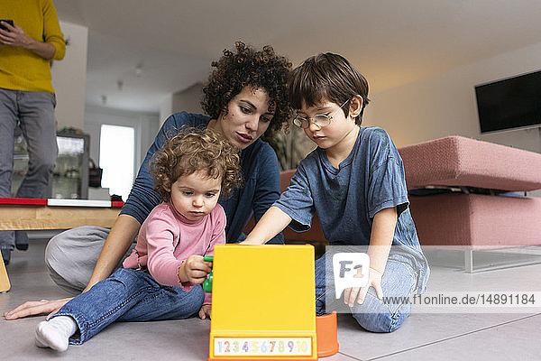 Mutter spielt und Kinder spielen mit einer Spielzeugkasse
