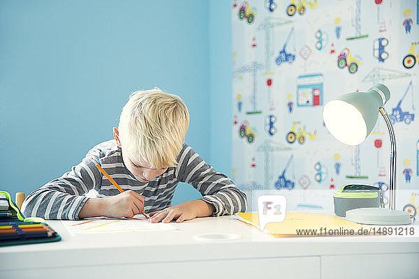 Fokussierter Junge macht Hausaufgaben am Schreibtisch im Kinderzimmer
