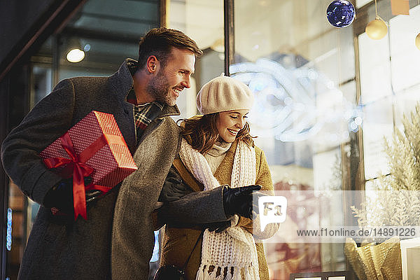 Smiling couple looking in shop window at Christmas time