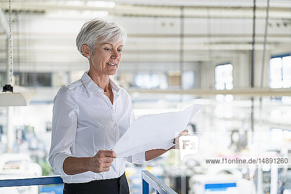 Senior woman looking at plan in a factory